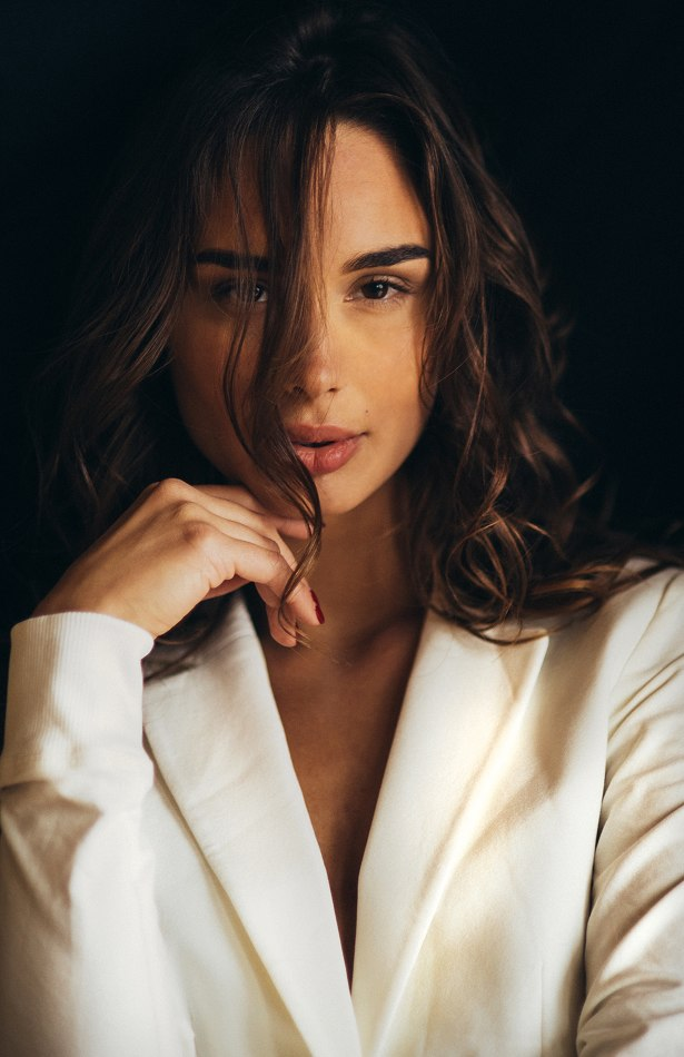 Female model dark background hair over some of face wearing white suit jacket