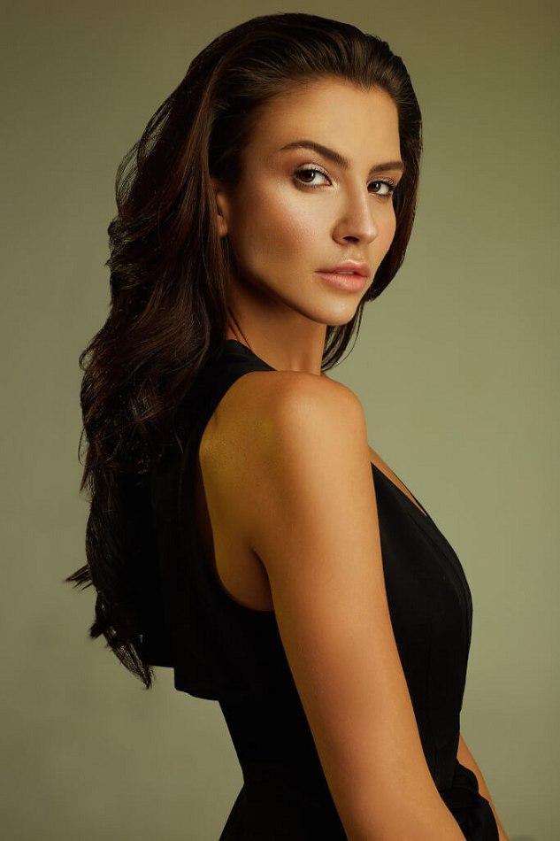 Female model standing looking over shoulder wearing black dress