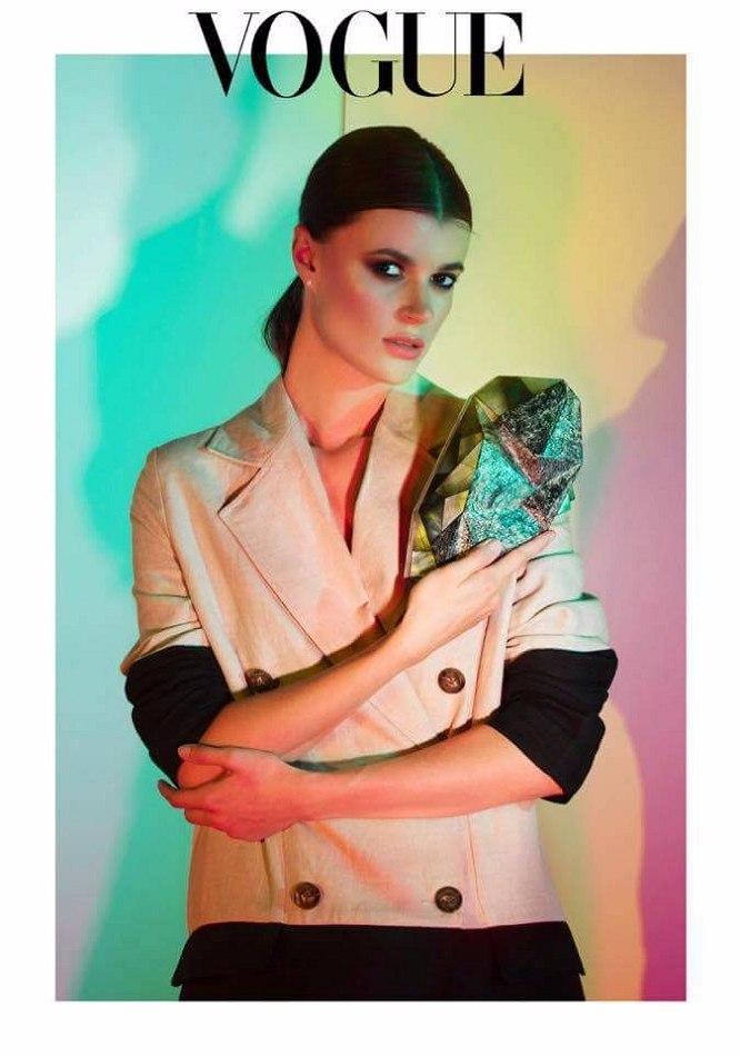 Vogue magazine cover female model standing white jacket multi coloured background