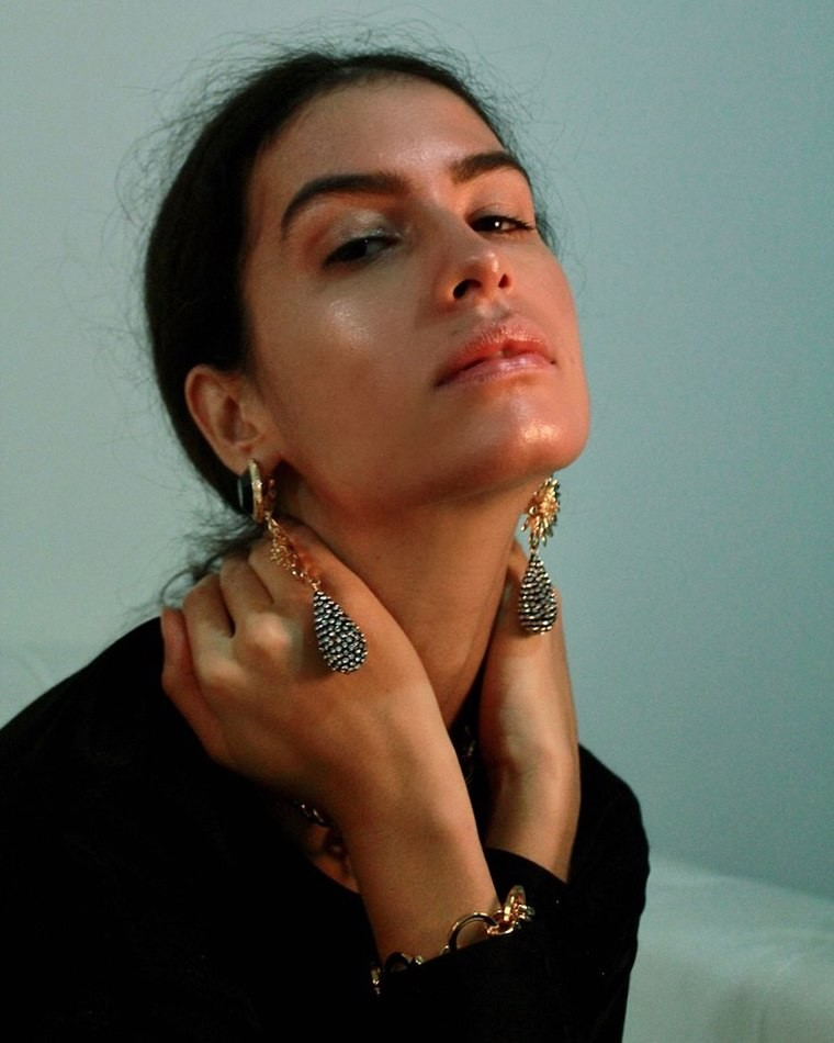 Female model sitting looking up hands on neck large wearing ear rings