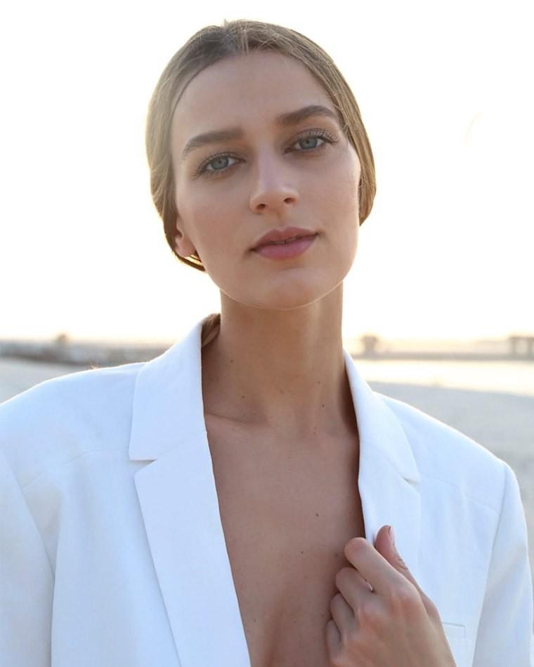 Female model outside in front of sun wearing white suit jacket