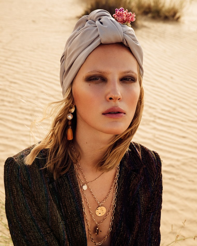 Female model on beach dunes wearing a scarf on head and black jacket
