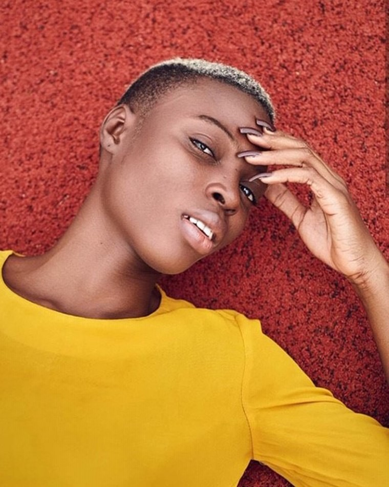 Female model laying down on red carpet wearing yellow top long finger nails