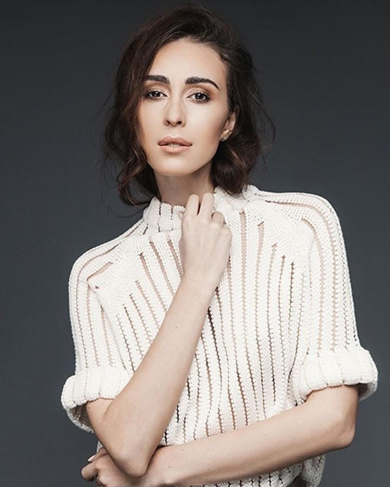 Female model standing wearing white top dark hair and dark background