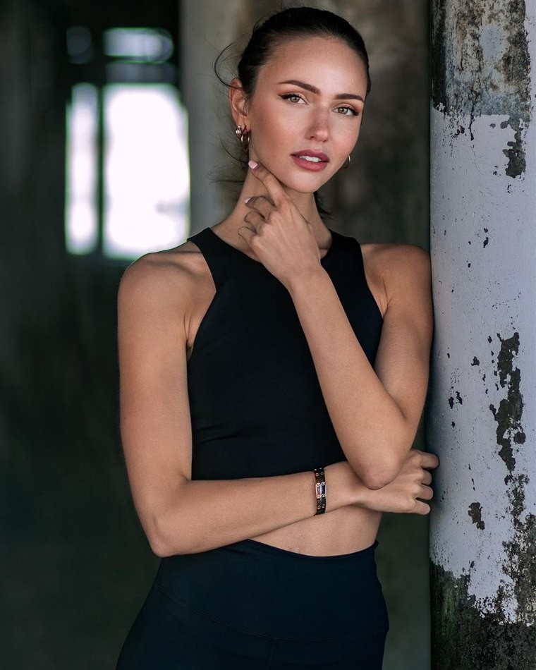 Female model blurry background black clothing arms across front
