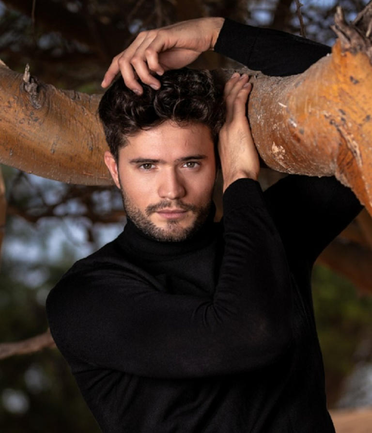 Male model standing next to tree with hands above head wearing dark clothing