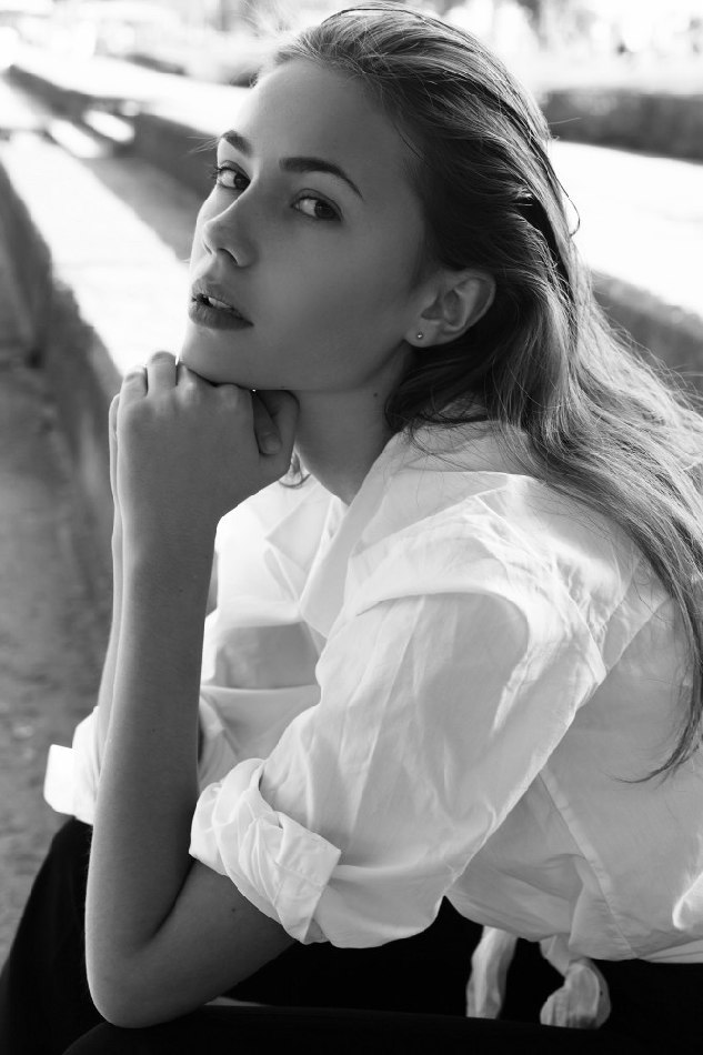 Female model black and white photo sitting wearing white shirt