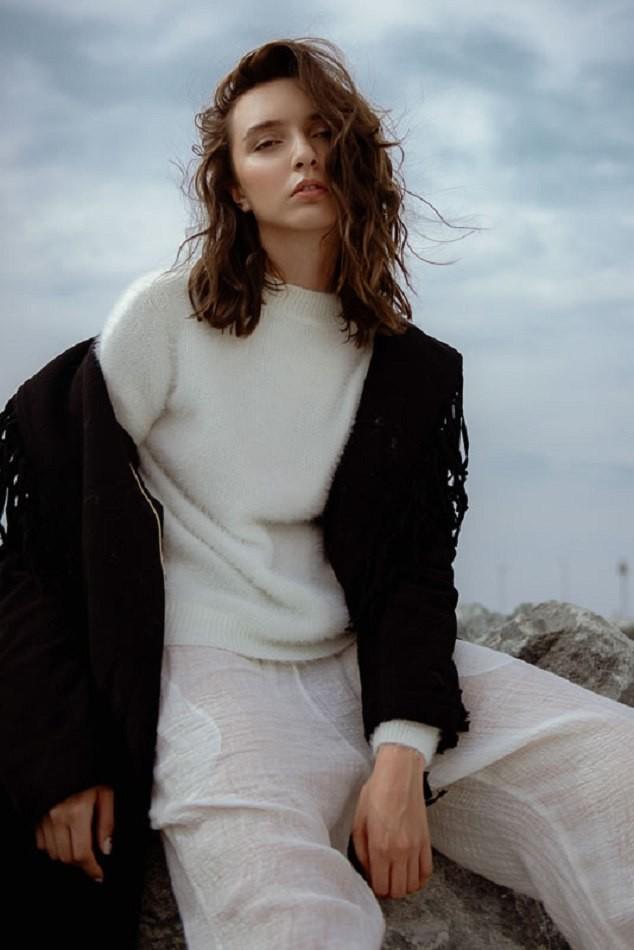 Female model sitting down sky background white clothing dark jacket over shoulders