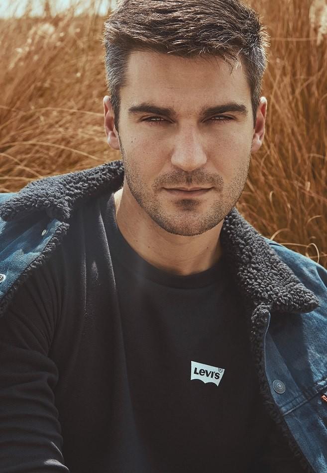 Male Model Slavko wearing blue jacket in front of grass