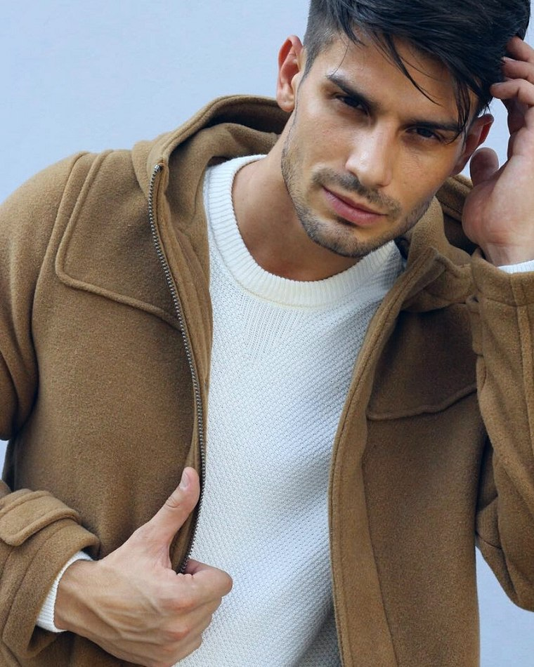 Male model Adrian standing wearing jacket over white jumper