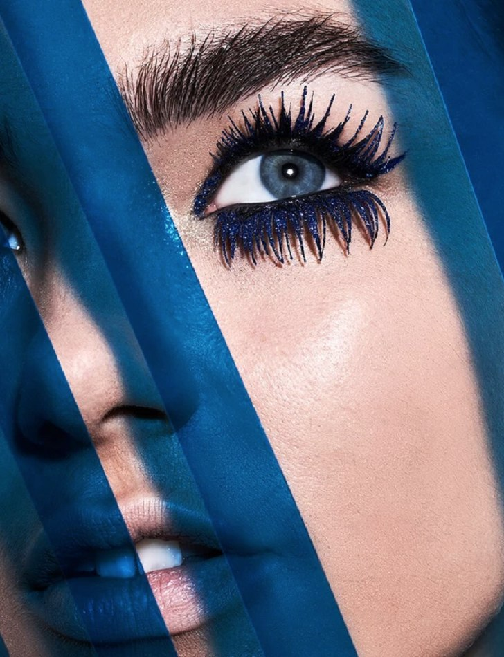 Female model very close up heavy eye lashes blue shadows over face
