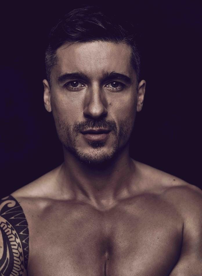 Male model Rastino tattoo on arm black background