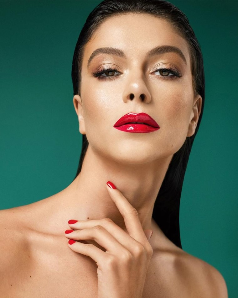 Female model close up green background dark hair red lipstick and red nails