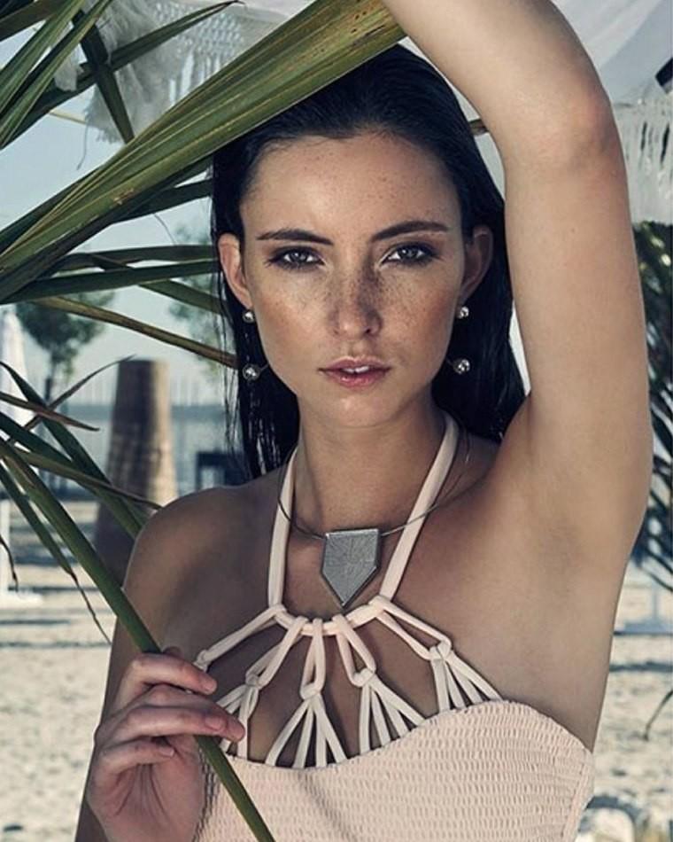 Female model on beach next to tree arm over head