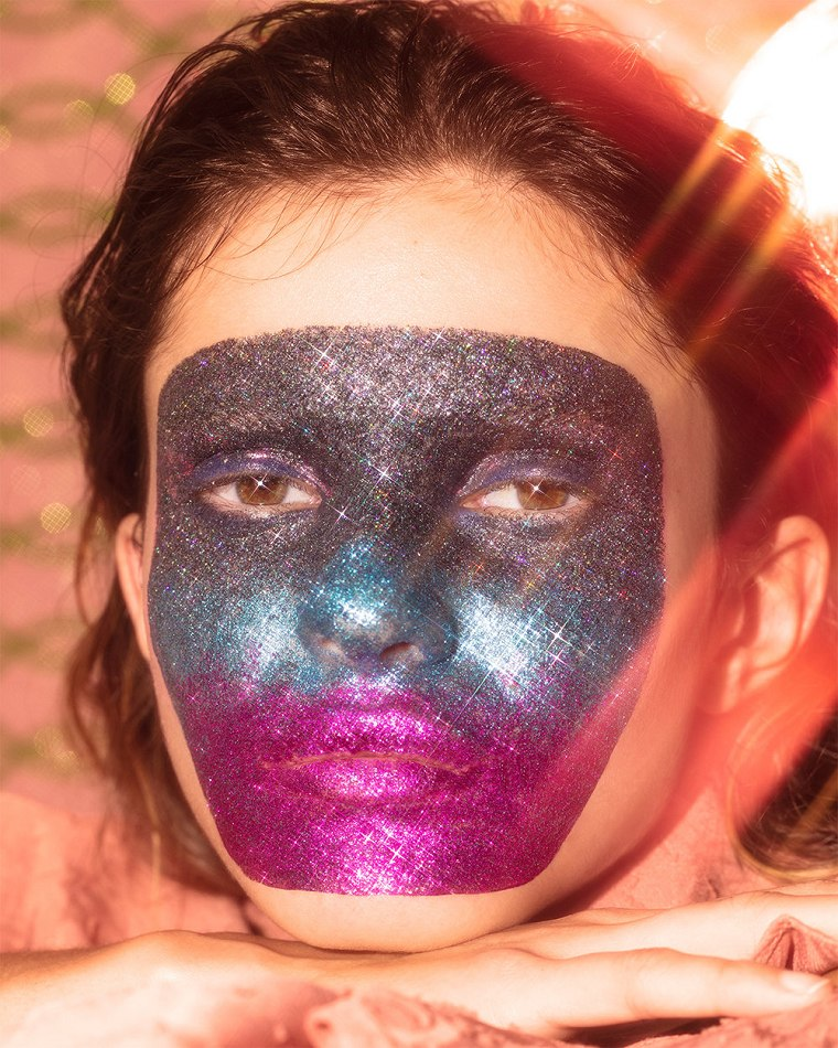 Female model close up resting head on hand glittering face paint and make up design