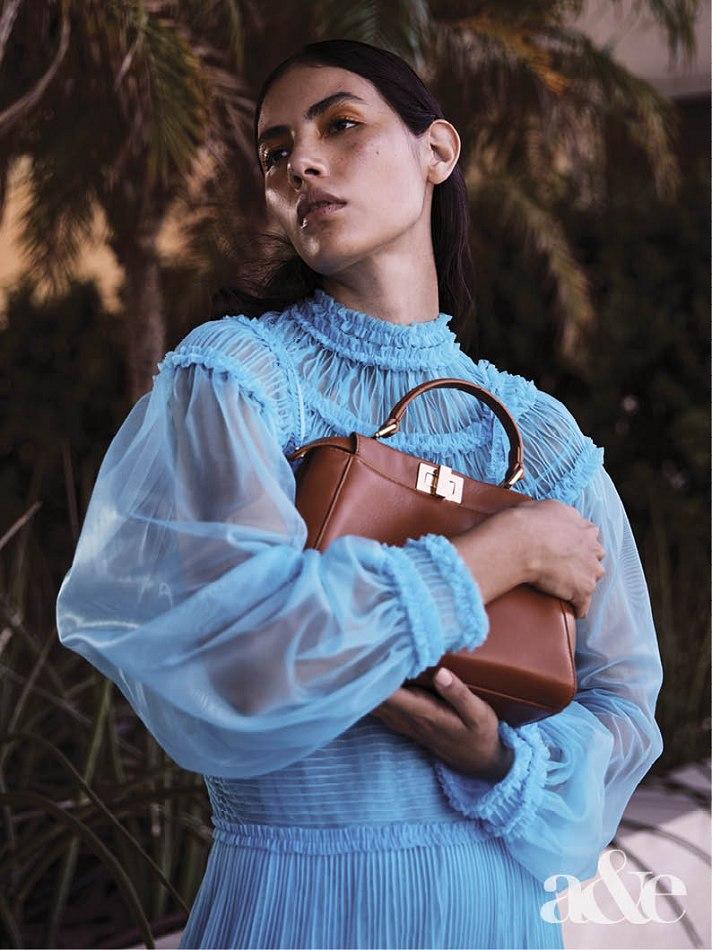 Female model standing wearing blue dress holding hand bag