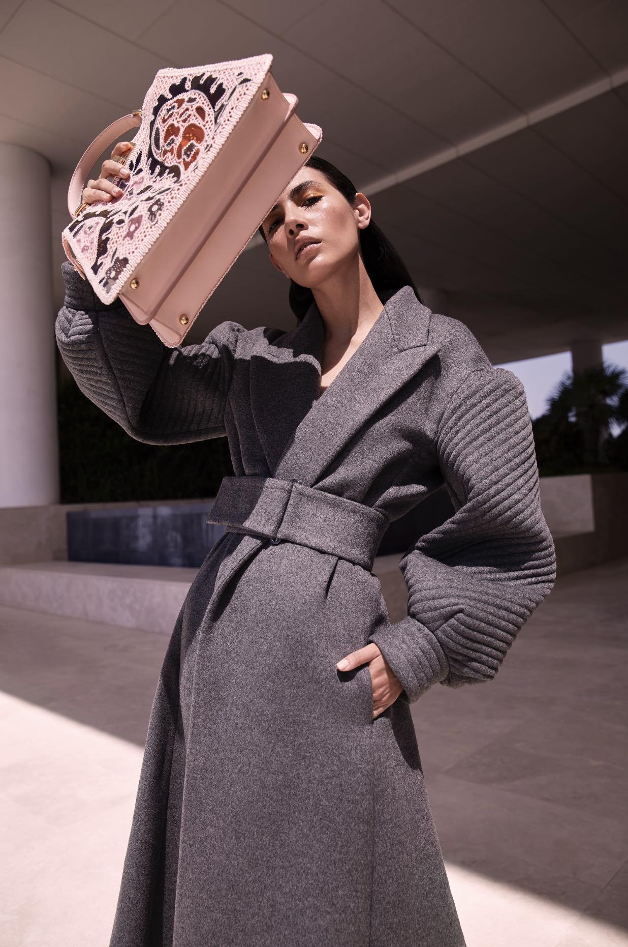 female model standing holding handbag up wearing long coat