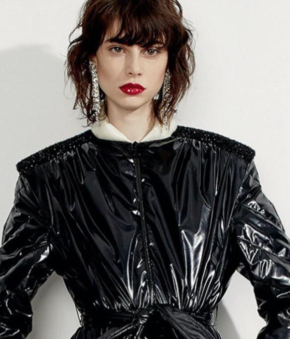 female model standing wearing black coat red lipstick