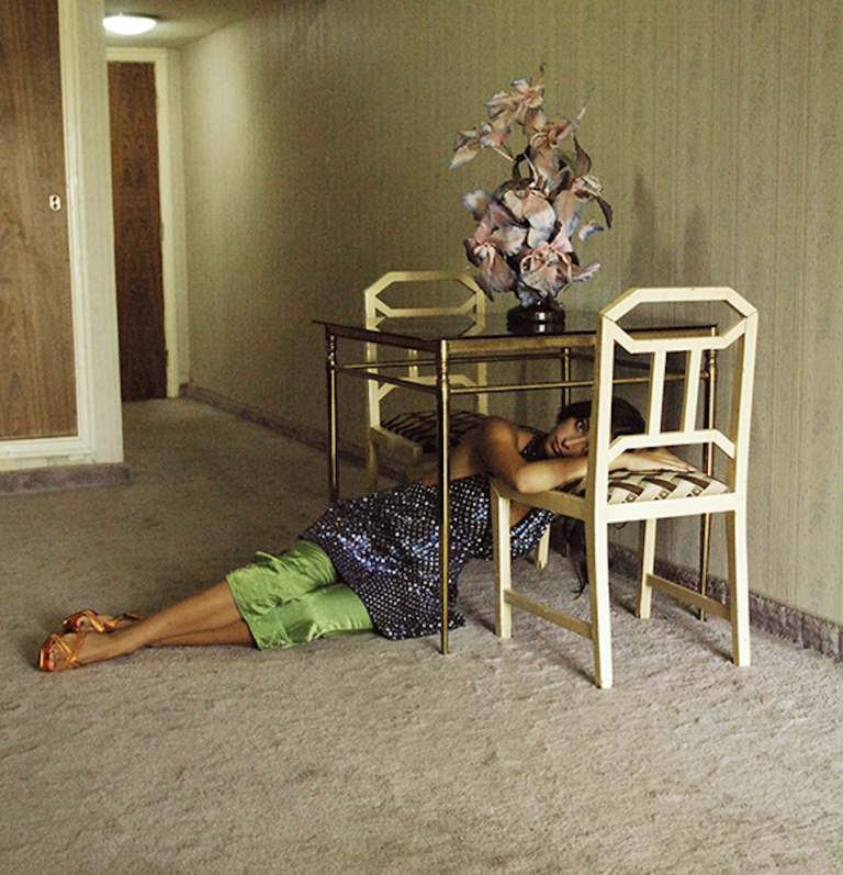 Female model laying on floor under table resting on chair