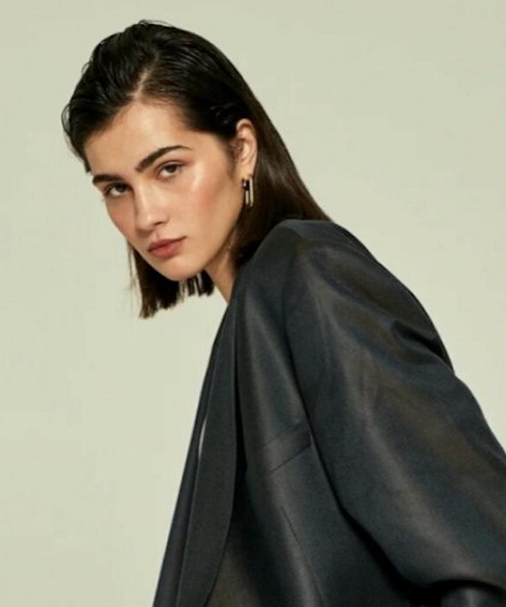 Female model dark hair white background wearing smart jacket