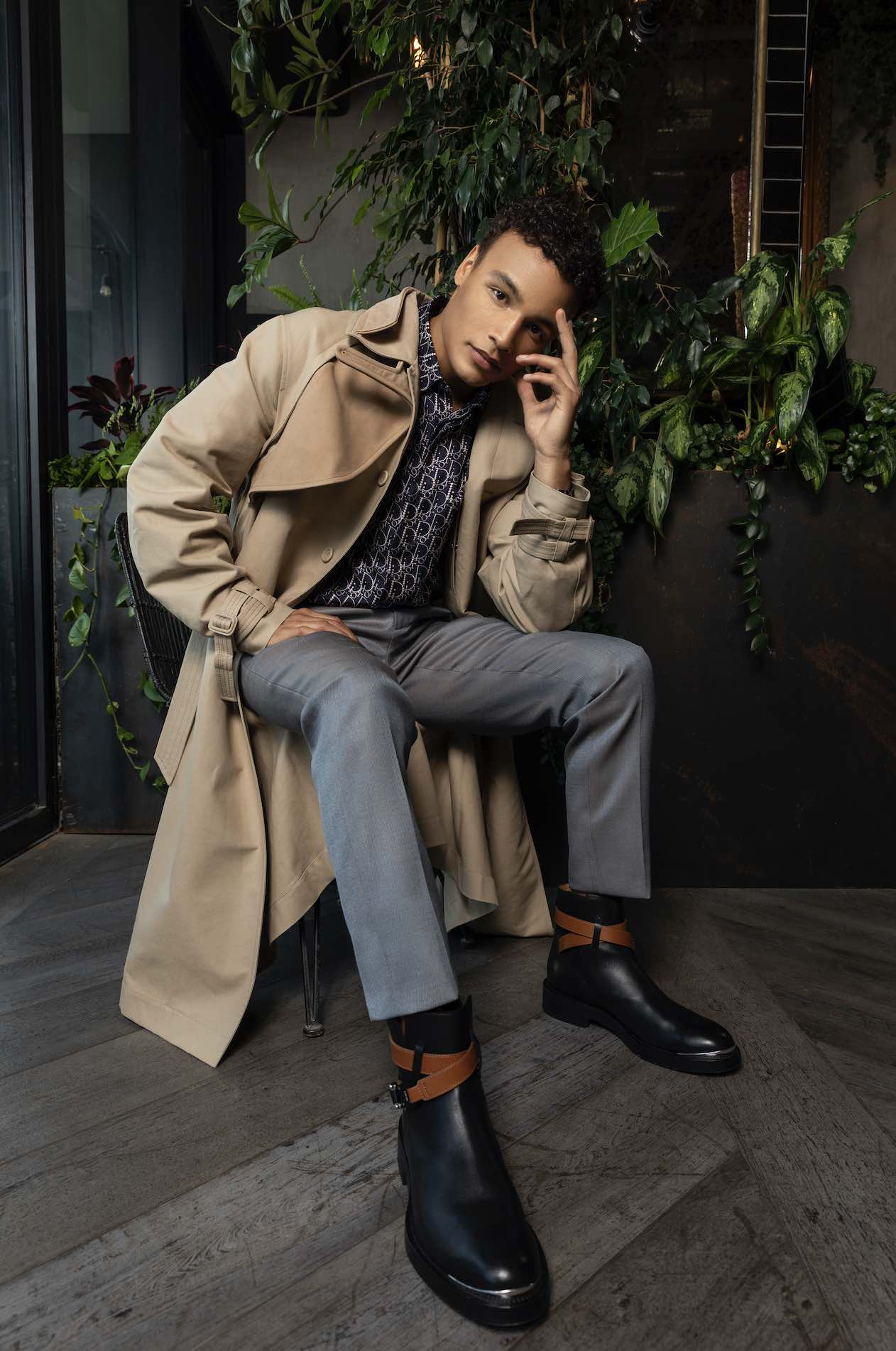 Male model sitting wearing long jacket trousers and shoes