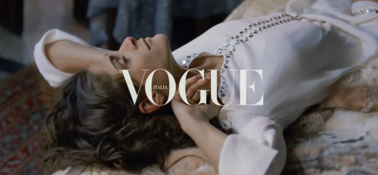 Vogue magazine female model laying down looking at ceiling wearing white dress